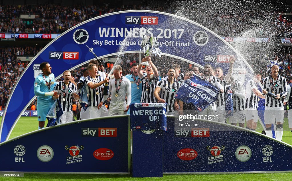 Millwall players celebrate victory and promotion with the trophy after during the Sky Bet League One Playoff Final between Bradford City and Millwall at Wembley Stadium on May 20, 2017 in London, England.