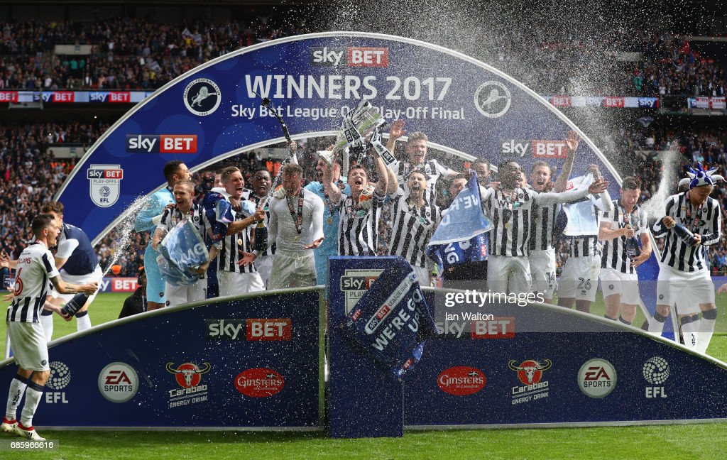 Millwall players celebrate victory and promotion with the trophy after the Sky Bet League One Playoff Final between Bradford City and Millwall at Wembley Stadium on May 20, 2017 in London, England.