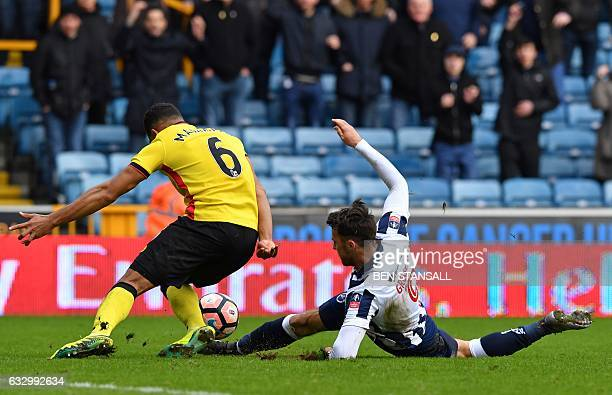 Millwall's English striker Lee Gregory and Watford's English-born Jamaican defender Adrian Mariappa compete for the ball in a goal-mouth scramble...