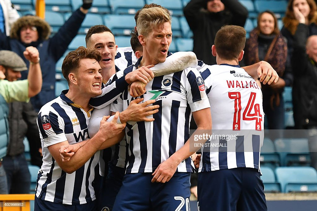 Millwall's English-born Welsh striker Steve Morison (C) celebrates with teammates after scoring the opening goal of the English FA Cup fourth round football match between Millwall and Watford at The Den in south London on January 29, 2017. / AFP / Ben STANSALL / RESTRICTED TO EDITORIAL USE. No use with unauthorized audio, video, data, fixture lists, club/league logos or 'live' services. Online in-match use limited to 75 images, no video emulation. No use in betting, games or single club/league/player publications. /