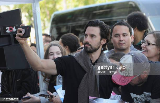 Milo Ventimiglia takes selfies with fans at Mandy Moore's Star Ceremony on the Hollywood Walk of Fame on March 25 2019 in Hollywood California