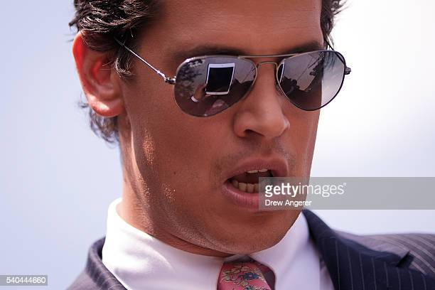 Milo Yiannopoulos a conservative columnist and internet personality looks at his tablet device during a press conference down the street from the...