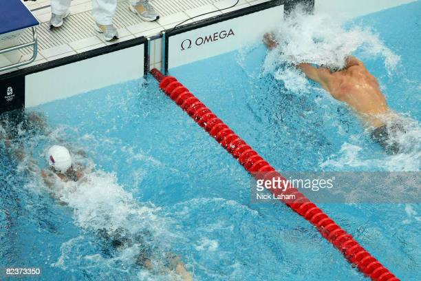 Milorad Cavic of Serbia and Michael Phelps of the United States reach for the wall in the Men's 100m Butterfly Final held at the National Aquatics...
