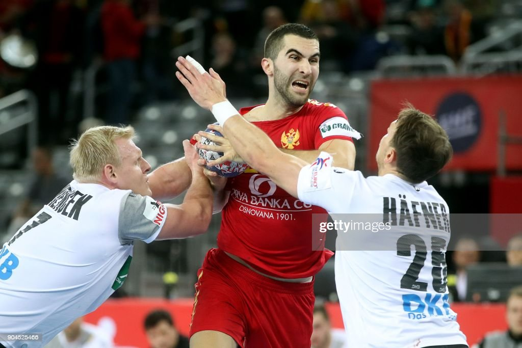 Milos Bozovic of Montenegro (C) vies with the ball with Patrick Wienck (L) and Kai Hafner (R) of Germany during the preliminary round group C match of the Men's 2018 EHF European Handball Championship between Germany and Montenegro in Zagreb on January 13, 2018. /