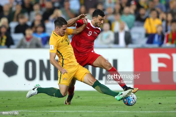 Milos Degenek of Australia tackles Omar Al Soma of Syria during the 2018 FIFA World Cup Asian Playoff match between the Australian Socceroos and...