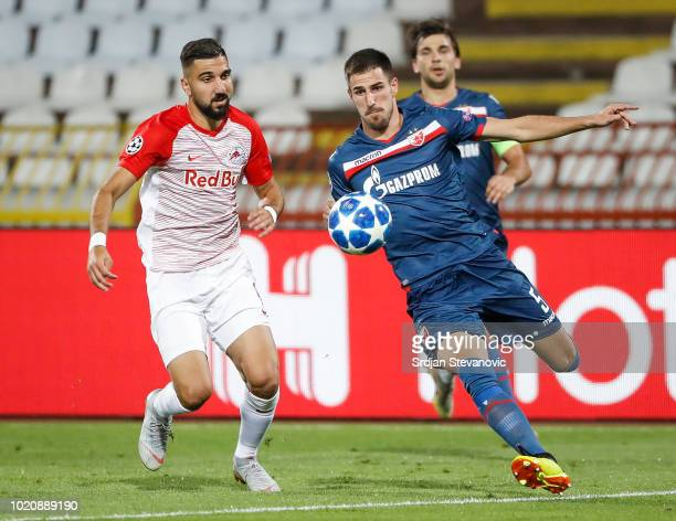 Milos Degenek of Crvena Zvezda in action against Munas Dabbur of Red Bull Salzburg during the UEFA Champions League Play Off First Leg match between...