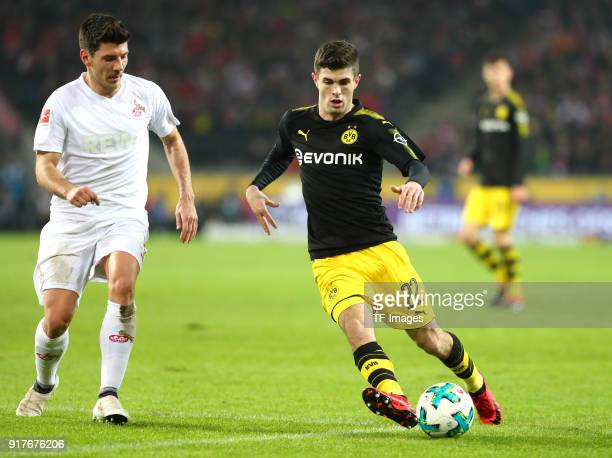 Milos Jojic of Koeln and Christian Pulisic of Dortmund battle for the ball during the Bundesliga match between 1 FC Koeln and Borussia Dortmund at...