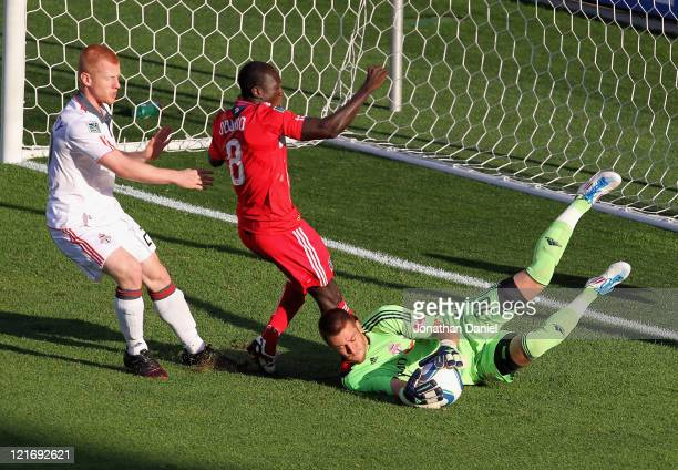 Milos Kocic of Toronto FC makes a save on a shot by Dominic Oduro of the Chicago Fire as Richard Eckersley defends during an MLS match at Toyota Park...
