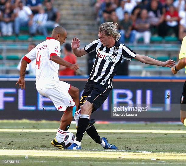 Milos Krasic of Juventus FC battles for the ball with Sergio Almiron of AS Bari during the Serie A match between Bari and Juventus at Stadio San...