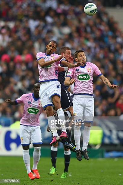 Milos Ninkovic and Saber Khlifa of Evian Thonon Gaillard squeeze out Gregory Sertic of Bordeaux during the French Cup Final match between Evian...