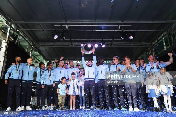 Milos Ninkovic holds aloft the ALeague trophy as Sydney FC players appear on stage in Pitt St Mall on May 8 2017 in Sydney Australia Sydney FC beat...