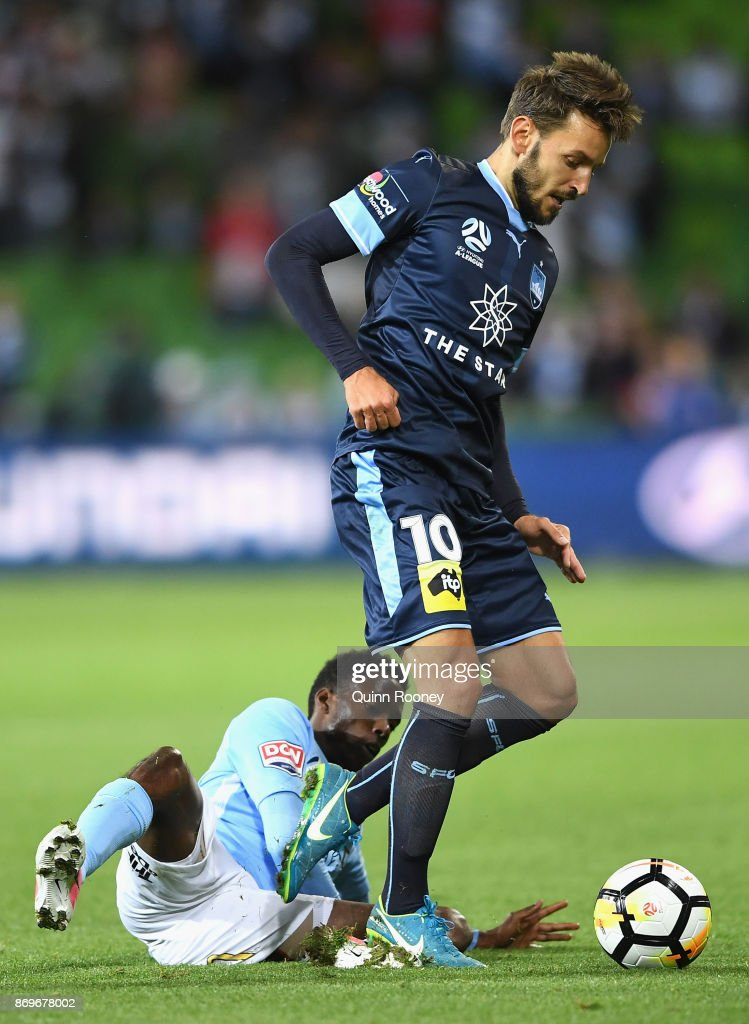 Milos Ninkovic of Sydney FC is tackled by Bruce Kamau of the City during the round five A-League match between Melbourne City FC and Sydney FC at AAMI Park on November 3, 2017 in Melbourne, Australia.