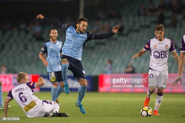 Milos Ninkovic of Sydney FC jumps out of this tackle by Glory's Mitchell Nichols during the round four ALeague match between Sydney FC and the Perth...