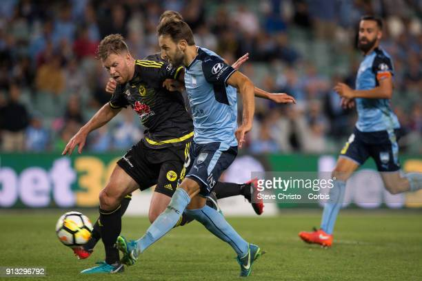 Milos Ninkovic of Sydney FC runs past Wellington's Daniel Mullen to score during the round 19 ALeague match between Sydney FC and the Wellington...