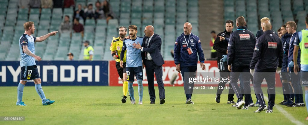 Milos Ninkovic of Sydney is restrained by Melbourne's coach Kevin Muscat when Victory's coaching staff ran on to the field of play after the winning goal was scored during the A-League Semi Final match between Sydney FC and Melbourne Victory at Allianz Stadium on April 28, 2018 in Sydney, Australia.