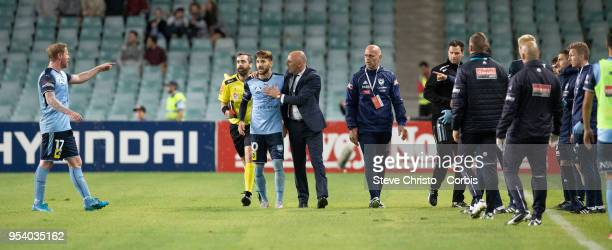 Milos Ninkovic of Sydney is restrained by Melbourne's coach Kevin Muscat when Victory's coaching staff ran on to the field of play after the winning...