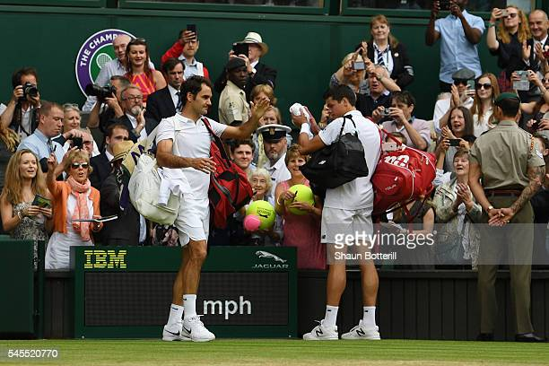 Milos Raonic of Canada and Roger Federer of Switzerland leave the court following the Men's Singles Semi Final match on day eleven of the Wimbledon...
