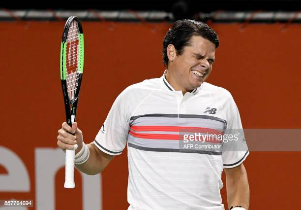 Milos Raonic of Canada grimaces during his men's singles second round match against Yuichi Sugita of Japan at the Japan Open tennis tournament in...