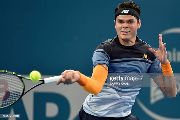 Milos Raonic of Canada hits a return against Croatia's Ivan Dodig during their men's singles match on the fifth day of the Brisbane International...