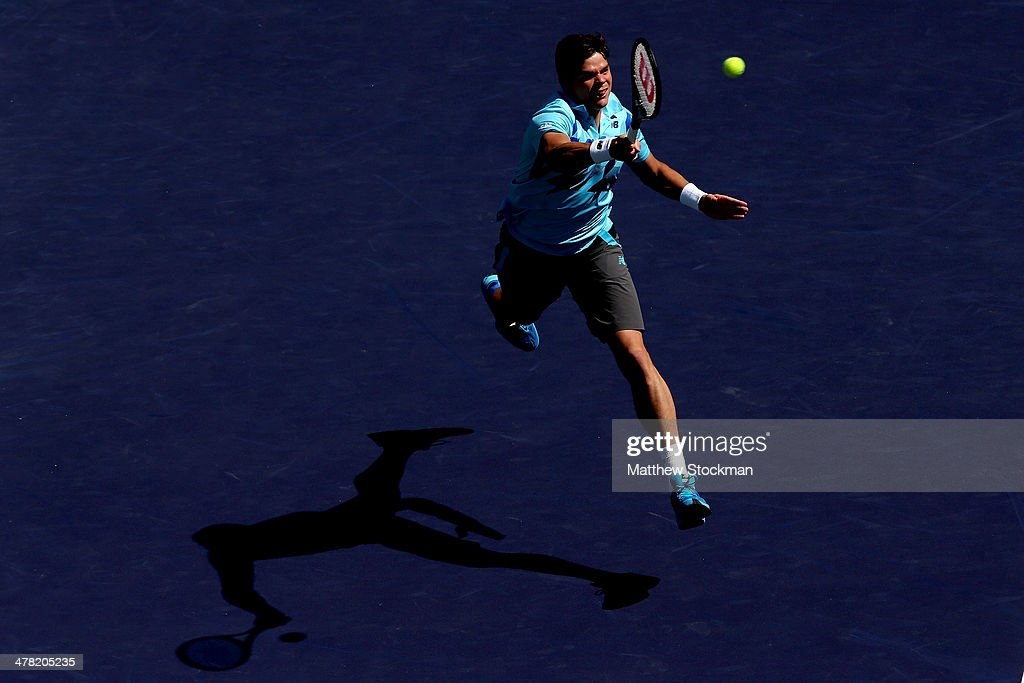 Milos Raonic of Canada leaps for a ball while playing Andy Murray of Great Britain during the BNP Parabas Open at the Indian Wells Tennis Garden on March 12, 2014 in Indian Wells, California.