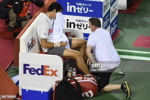 Milos Raonic of Canada receives medical attention during his match against Yuichi Sugita of Japan on day four of the Rakuten Open at Ariake Coliseum...