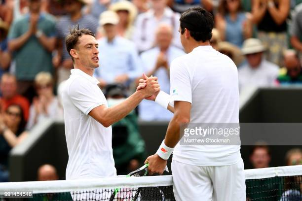 Milos Raonic of Canada shakes hands with John Millman of Australia after their Men's Singles second round match on day three of the Wimbledon Lawn...
