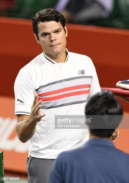Milos Raonic of Canada shakes hands with Yuichi Sugita of Japan during his men's singles second round match at the Japan Open tennis tournament in...
