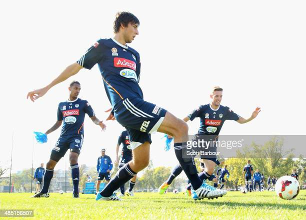 Milos Ridisec of the Victory passes the ball as Nick Ansell and Rashid Mahazi look on during a Melbourne Victory ALeague training session at Gosch's...