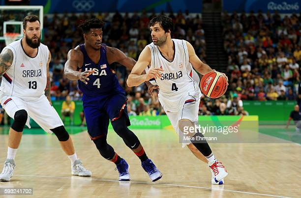 Milos Teodosic of Serbia drives the ball around Jimmy Butler of United States during the Men's Gold medal game on Day 16 of the Rio 2016 Olympic...