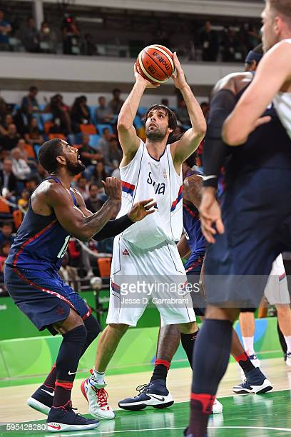 Milos Teodosic of Serbia shoots against Kyrie Irving of the USA Basketball Men's National Team during the Gold Medal Game on Day 16 of the Rio 2016...