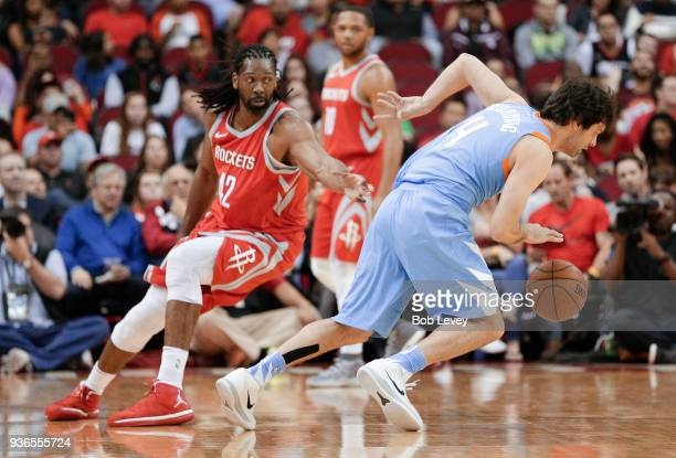 Milos Teodosic of the LA Clippers drives around Nene of the Houston Rockets at Toyota Center on March 15 2018 in Houston Texas NOTE TO USER User...