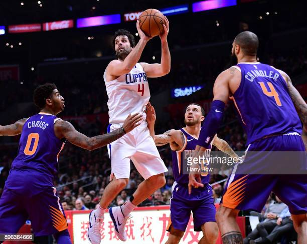 Milos Teodosic of the LA Clippers looks to pass between Marquese Chriss Alan Williams and Tyson Chandler of the Phoenix Suns during the first half at...