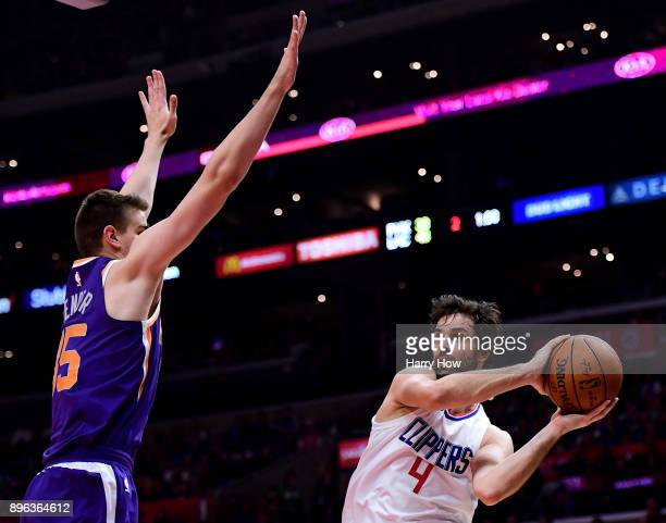 Milos Teodosic of the LA Clippers passes around Alan Williams of the Phoenix Suns during the first half at Staples Center on December 20, 2017 in Los...