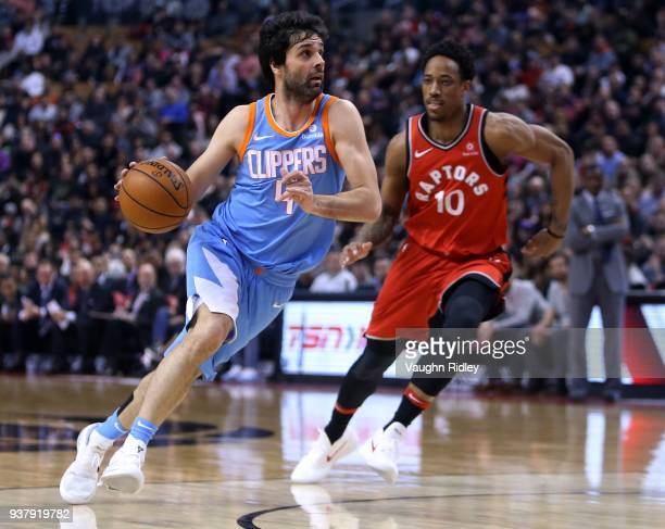 Milos Teodosic of the Los Angeles Clippers dribbles the ball as DeMar DeRozan of the Toronto Raptors defends during the first half of an NBA game at...