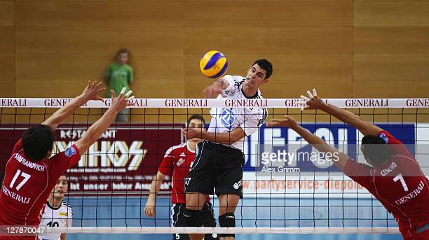 Milos Vemic of Friedrichshafen smashes as Alexander Shafranovich and Fredy Cedeno of Unterhaching block during the Volleyball Bundesliga match...