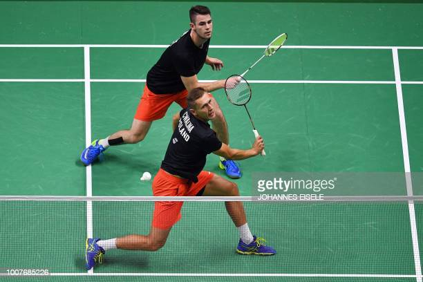 Milosz Bochat of Poland watches teammate Adam Cwalina reach for a shot against Han Chengkai and Zhou Haodong of China in their men's doubles match...