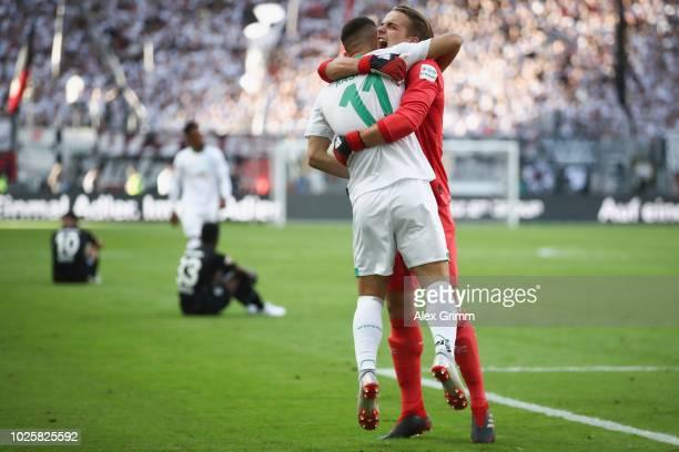 Milot Rashica of Bremen celebrates with team mate Luca Plogmann after the Bundesliga match between Eintracht Frankfurt and SV Werder Bremen at...