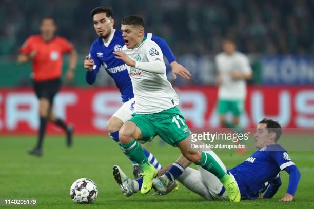 Milot Rashica of Bremen is challenged by Sebastian Rudy and Suat Serdar of Schalke during the DFB Cup quarterfinal match between FC Schalke 04 and...