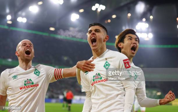 Milot Rashica of SV Werder Bremen celebrates as he scores his team's first goal from a penalty with Yuya Osako and Davy Klaassen during the...