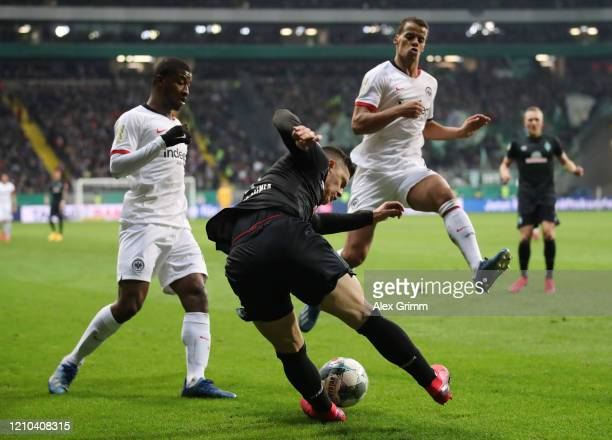 Milot Rashica of SV Werder Bremen tries to clear the ball from Almamy Toure and Timmy Chandler of Eintracht Frankfurt during the DFB Cup quarterfinal...