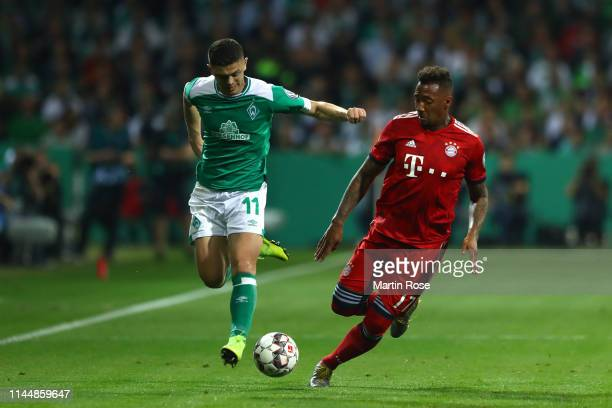 Milot Rashica of Werder Bremen and Jerome Boateng of Bayern Munich battle for possession during the DFB Cup semi final match between Werder Bremen...