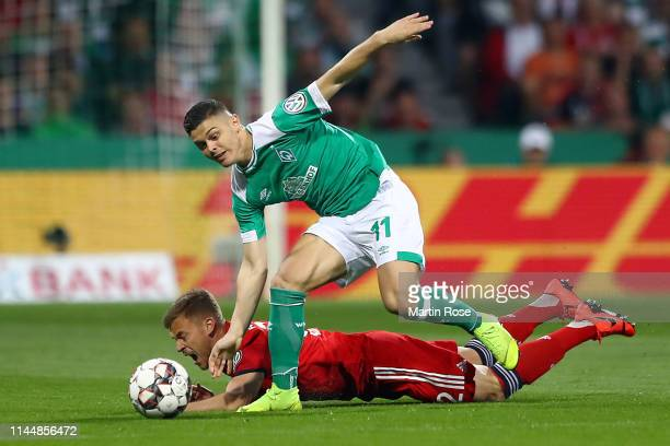 Milot Rashica of Werder Bremen and Joshua Kimmich of Bayern Munich battle for possession during the DFB Cup semi final match between Werder Bremen...