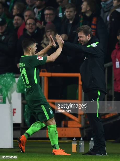 Milot Rashica of Werder Bremen celebrates scoring his side's second goal with head coach Florian Kohfeldt during the Bundesliga match between SV...
