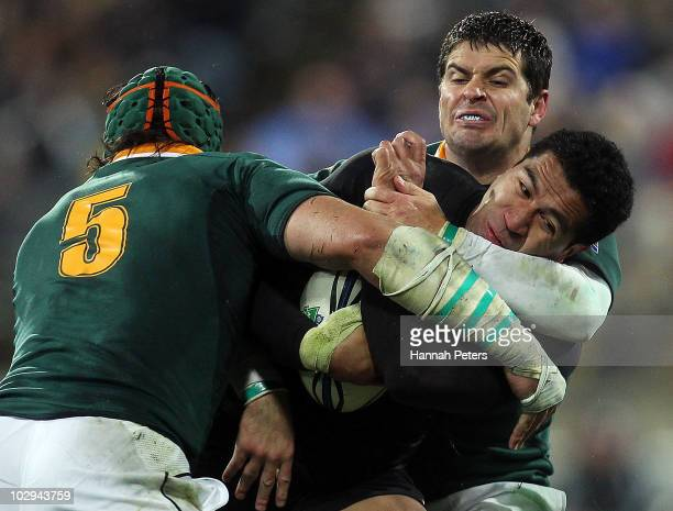 Mils Muliaina of the All Blacks is hit hard by Morne Steyn and Victor Matfield of the Springboks during the TriNations match between the New Zealand...