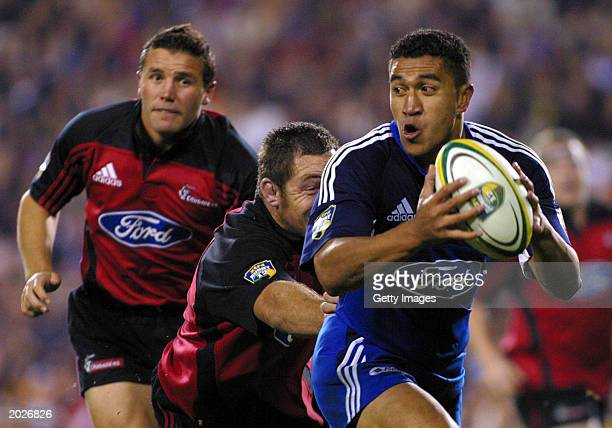 Mils Muliaina of the Blues looks to pass the ball as he runs from Aaron Mauger and Mark Hammett of the Crusaders during the Super 12 final game...