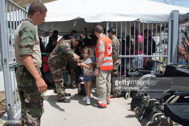 Miltary and Red Cros staff show a girl the way during an evacuation to Guadeloupe island at the Grand Case l'Esperance airport on the French...