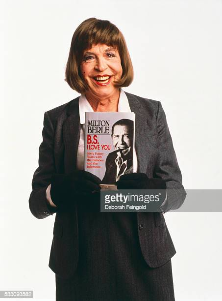 Milton Berle, dressed in drag, holds his 1987 book entitled B.S. I Love You: Sixty Funny Years with the Famous and the Infamous.