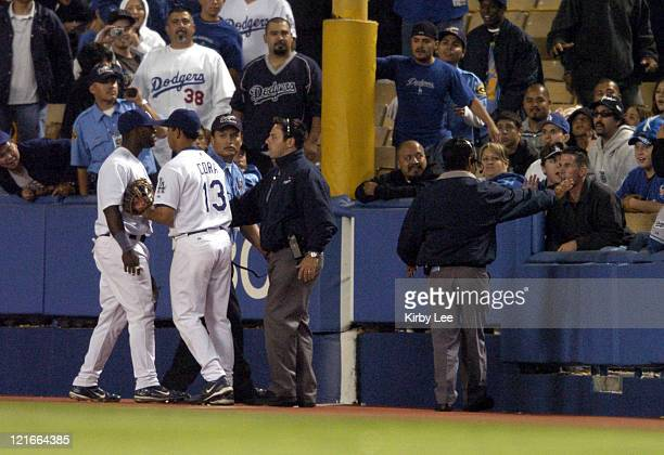Milton Bradley of the Los Angeles Dodgers is restrained by Alex Cora after a beer bottle was thrown at the right fielder after dropping a fly ball in...