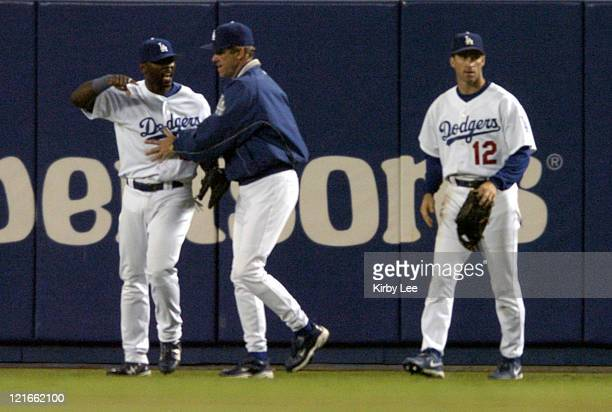 Milton Bradley of the Los Angeles Dodgers is restrained by manager Jim Tracy after a beer bottle was thrown at the right fielder after dropping a fly...