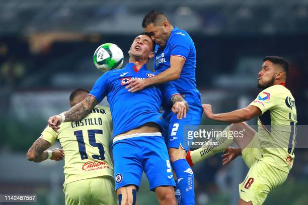 Milton Caraglio and Pablo Aguilar of Cruz Azul struggles for the ball with Nicolas Castillo and Bruno Valdez of America during the quarterfinals...
